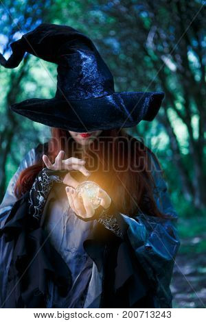 Photo of witch in long hat with glowing magic ball at dark evening forest