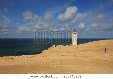 Old lighthouse partly covered by a high sand dune. Rubjerg Knude Denmark.