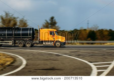 Orange truck with a tank rides on the highway, blurred background, selective focus on the truck