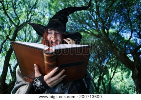 Photo of witch casting spell, with open book in evening mystical forest