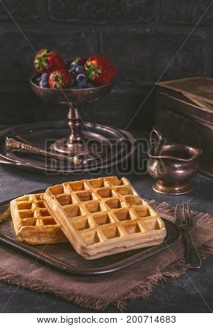 Fresh Belgian waffles without garnish on vintage tray in dark tones