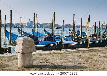 Old stone mooring bollard on quay of Venetian lagoon