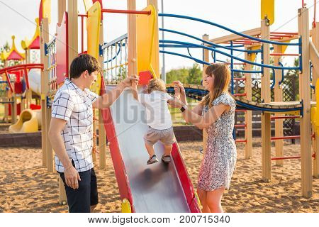 Happy parents with son playing at children's slide.
