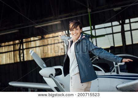 Cheerful Pilot Posing With A Small Aircraft