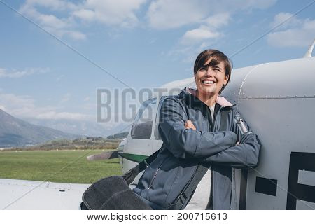 Smiling Female Pilot Posing With Her Plane