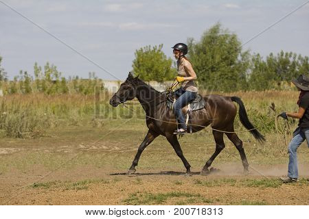 Horseback riding lessons - young woman riding a horse, telephoto shot