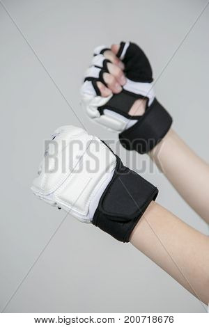 Protection for taekwondo & judo. Hands in gloves on a gray background