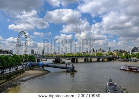 London United Kingdom - May 2 2017: Festival Pier with Millennium Wheel and Hungerford Bridge. Nice cloudy and blue sky with river boats.