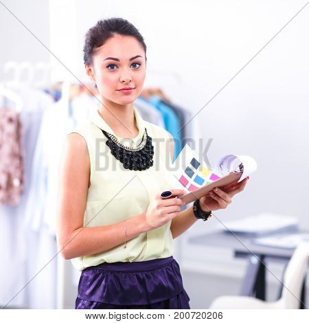 Young fashion designer with folder working at studio
