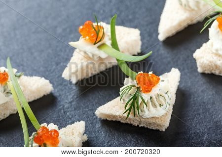 Appetizer canape with red caviar and cream cheese on stone slate background close up. Delicious snacks sandwiches crostini brushetta antipasti on party or picnic time. Top view