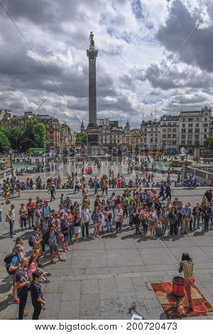 Trafalgar Square London UK - July 21 2017: Street performer with large crowd watching.Taken from the National Portrait Gallery.