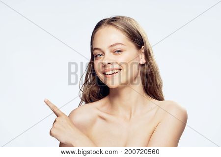 Beautiful young woman on white isolated background shows on empty space.