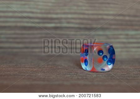 Single transparent dice on wooden board. Six sides with blue and red points.
