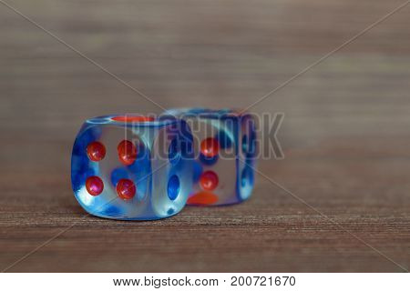 Two transparent dices on wooden board. Six sides with blue and red points.