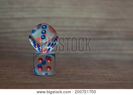 Two transparent dices on each other on wooden board. Six sides with blue and red points.