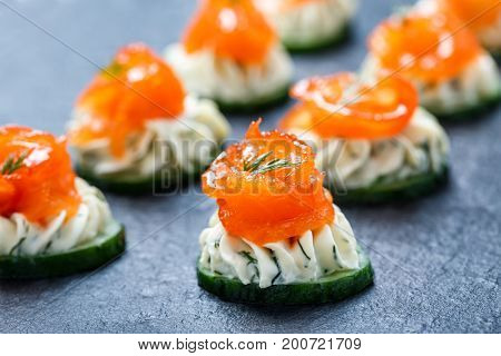 Appetizer canape with salmon cucumber and cream cheese on stone slate background close up. Delicious snacks sandwiches crostini brushetta antipasti on party or picnic time. Top view