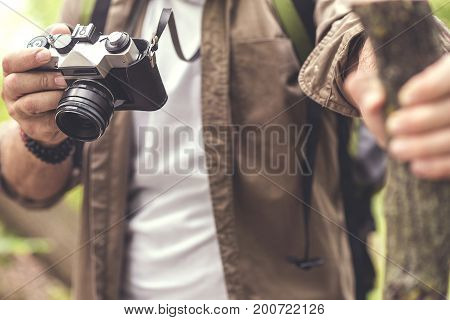 Close up of male hands photographing nature while standing with wooden stick. Focus on retro camera