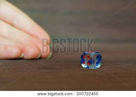 Woman hand trowing transparent dice to brown wooden board. Six sides with blue and red points. Blurry background.