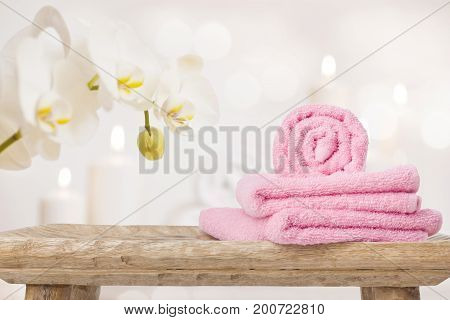 Spa towels on wooden table and orchid over abstract background