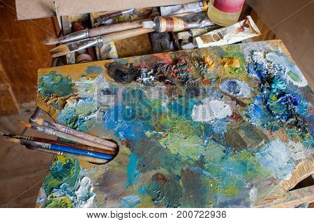 The artist's palette covered with colors with tassels lying on the sketchbook.