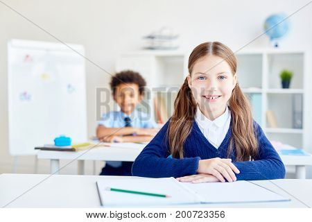 Pretty scholar sitting by desk with classmate on background