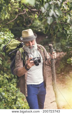 Top view of joyful old bearded man taking photos in forest. He is looking at scene through camera and laughing. Traveler is carrying rucksack