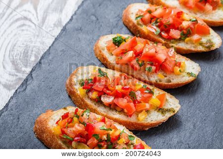 Appetizer bruschetta with chopped vegetables on ciabatta bread on stone slate background close up. Delicious snacks sandwiches crostini canape antipasti on party or picnic time. Top view