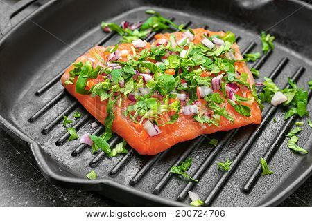 Grill frying pan with slice of salmon and herbs, closeup