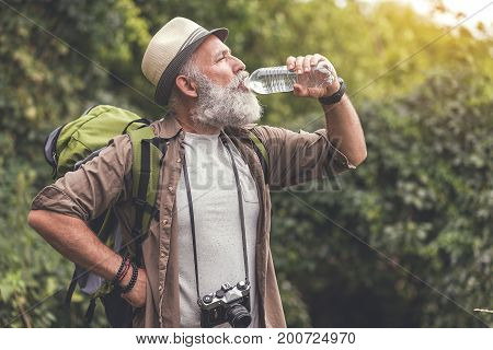 Profile of thirsty mature male tourist enjoying fresh beverage while standing in forest. Copy space