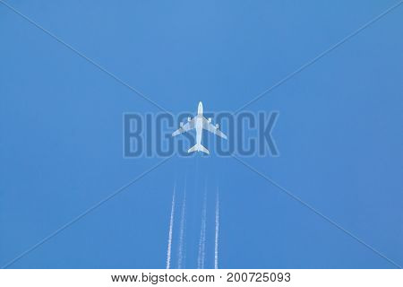 Passenger jet airplane with contrail or vapour trail against clear blue sky.