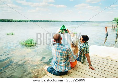Group of young people sitting on the dock near the lake, toasting with bottles, drinking beer and smiling. Men and woman chatting, relaxing, enjoying sunset. Friendship, having fun oktoberfest concept  vzroslyiвзрослыйalkogholalkoghol nyi napitokspirtалко