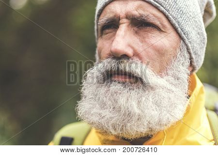 Close up portrait of stern face of mature male bearded tourist thinking about nature. He is looking forward pensively. Copy space