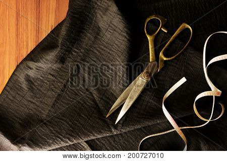 Measuring and cutting textile or fine cloth. Work table of a tailor. Gold scissors, measure tape and black silky fabric. Intentionally shot in retro muted color.
