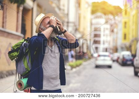 Concentrated old male tourist taking photos on urban architecture. He is standing on street and carrying backpack. Copy space