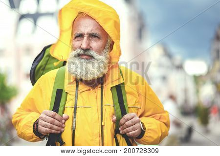Portrait of pensive senior male tourist walking in town with backpack. He is wearing hood to protect him from the wind. Copy space