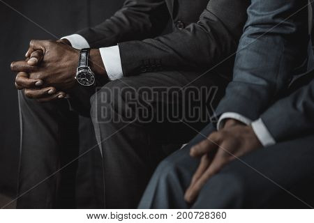 partial view of multiethnic business people in suits waiting for job interview