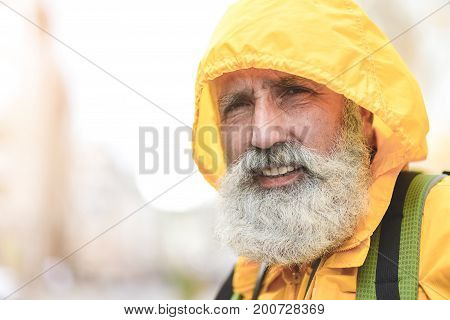 Close up portrait of cheerful senior man standing outdoors while it is raining. He is wearing raincoat yellow and smiling. Traveler is carrying rucksack. Copy space