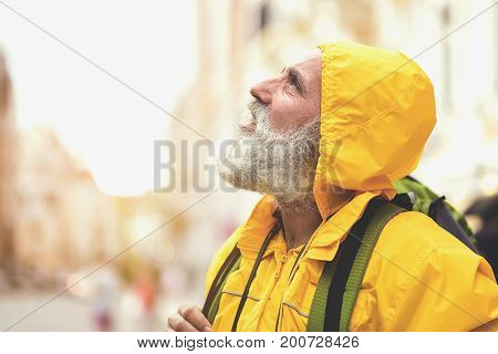 It is going to be rain. Thoughtful old male traveler is looking at the sky with expectation. He is standing with touristic backpack on street. Copy space