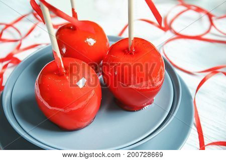 Plate with delicious candy apples on table, closeup