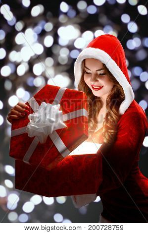 Snow Maiden in red suit smiling holding a gift, opens a gift on a dark background, portrait.
