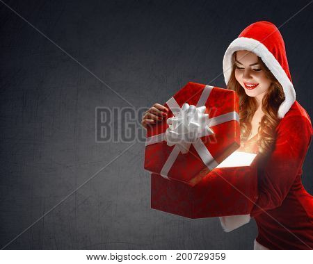 Snow Maiden in red suit smiling holding a gift, opens a gift on a dark background, portrait. 2018