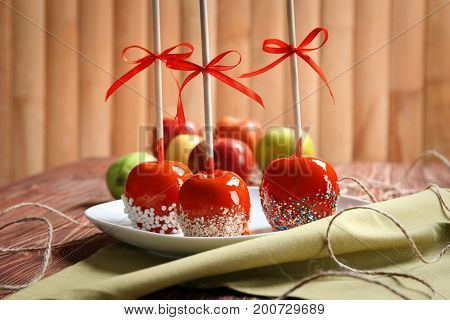 Plate with delicious candy apples on wooden table
