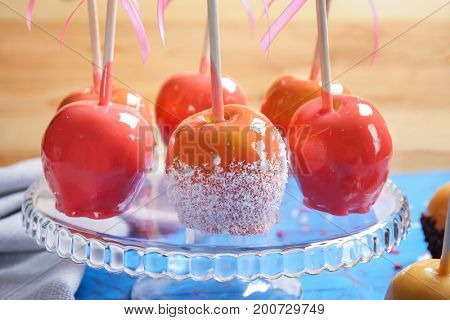 Glass stand with delicious candy apples, closeup
