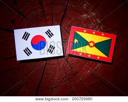 Grenada Flag With South Korean Flag On A Tree Stump Isolated