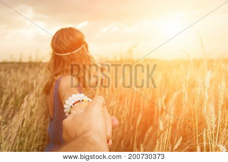 Girl holding her boyfrined in nature - wheat field. Focus is on the hands.