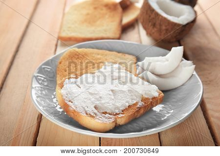 Delicious toasts with coconut oil in plate on wooden table