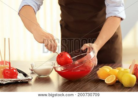 Young woman preparing toffee apples in kitchen