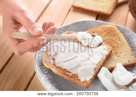 Female hand holding spoon with coconut oil above delicious toasts in plate