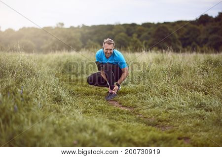 An exercising man in fit wear while running outdoors stop to clutch an injured ankle.