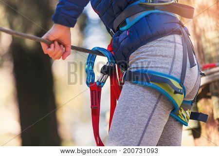 Close up climbing equipment. Girl in adventure park